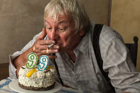 99: Naughty old pensioner lighting his cigarette on his birthday cake