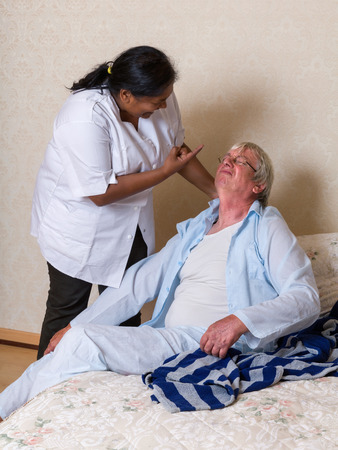 Nurse in old peoples home shouting at an elderly man while helping him into bed