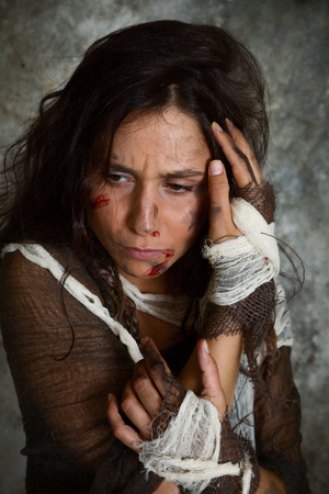 beaten: Homeless young woman dressed in rags in a derelict building