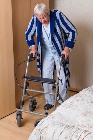 home nursing: Elderly grandfather in nursing home using a rollator in his pajama