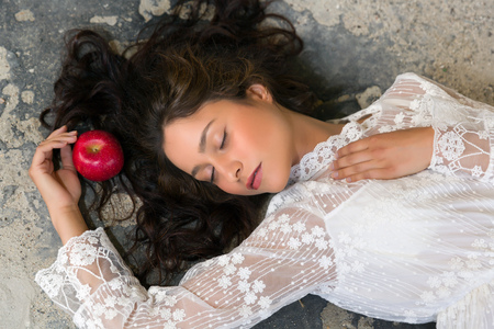 girl apple: Stunning young woman in white lace dress lying on the floor with a red apple