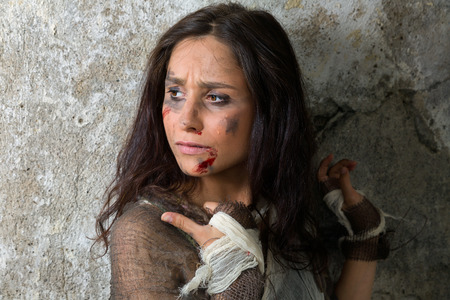 Dakloze jonge vrouw, gekleed in lompen in een vervallen gebouw
