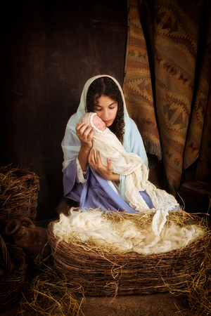 nacimiento de jesus: Chica adolescente jugando el papel de la Virgen Mar�a con una mu�eca en una escena viva de la natividad de Navidad