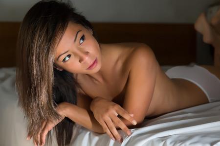 ragazza nuda: Giovane donna asiatica nuda in mutandine bianche sdraiato su un letto con lenzuola rugosa