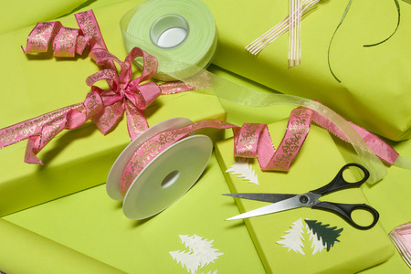 decorar: Table full of wrapping paper, ribbons and bows to decorate presents Foto de archivo