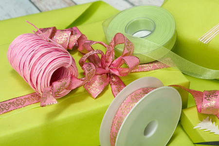 Table full of wrapping paper, ribbons and bows to decorate presents Stock Photo