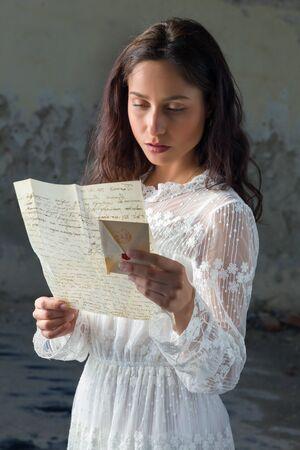 donna innamorata: Giovane donna in abito di pizzo antico leggendo una lettera triste Archivio Fotografico