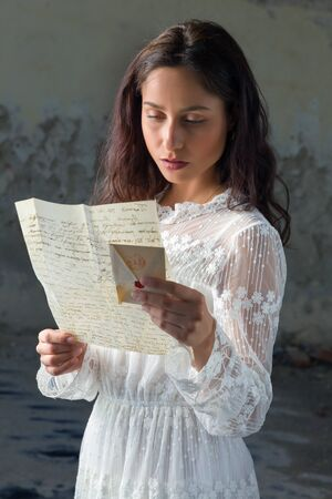 letter: Young woman in antique lace dress reading a sad letter