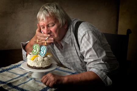 wrinkled: Old pensioner lighting his cigarette on his birthday cake.
