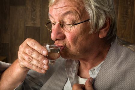 alcoholismo: Gray anciano disfrutando de una copa de ginebra en un vaso de chupito