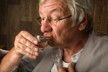 alcoholism: Gray elderly man enjoying a jenever drink in a shot glass Stock Photo