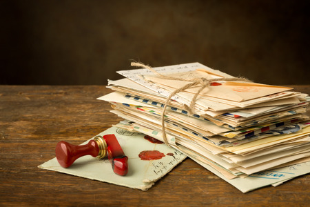 Wax seal next to a bundle of old letters on an antique wooden table Stockfoto