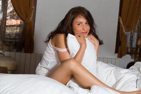 jungen unterw�sche: Auf Schlafzimmer mit einer jungen Frau sitzt auf ihrem Bett mit einem Kissen