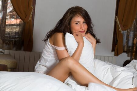 young woman in underwear: View on bedroom with a young woman sitting on her bed with a pillow