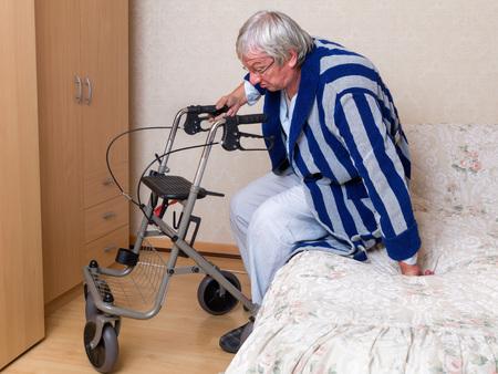 Ouderen grootvader in het verpleeghuis met behulp van een rollator in zijn pyjama