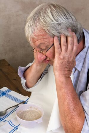 grumpy old man: Lonely elderly man disliking his porridge breakfast in the morning Stock Photo