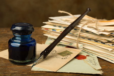 bundle of letters: Vintage ink well and fountain pen on a table with old letters