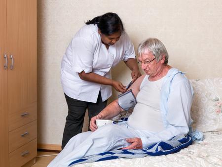 enfermeras: Enfermera que controla la presi�n arterial de Amigos de un anciano en una residencia de ancianos Foto de archivo