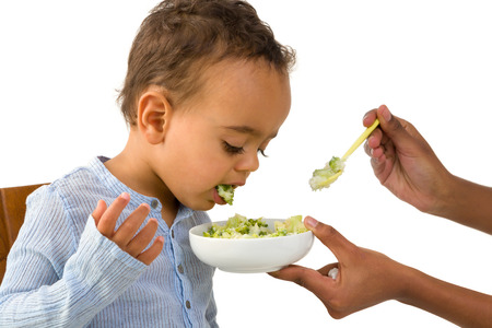 Little 18 month African toddler boy refusing to eat his vegetables Standard-Bild