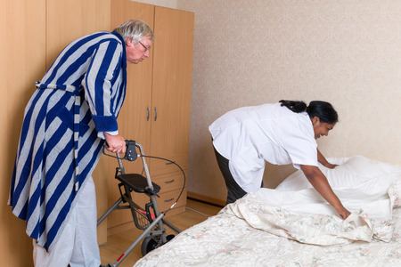 Naughty grandpa in nursing home admiring the nurses butt Stock Photo