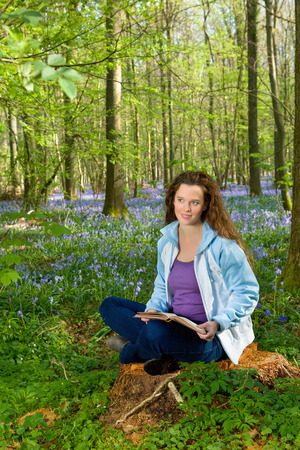 long hair: Attractive young woman among millions of bluebells wildflowers Stock Photo