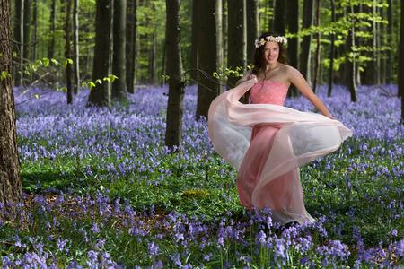 fiori di campo: Innocenzo giovane donna con abito rosa fata in una foresta campanule primavera Archivio Fotografico
