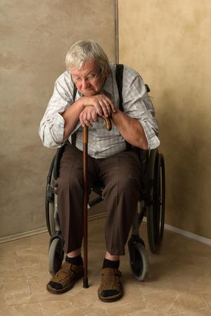 hombre solitario: Anciano solo en hogar de ancianos apoyado en su bastón