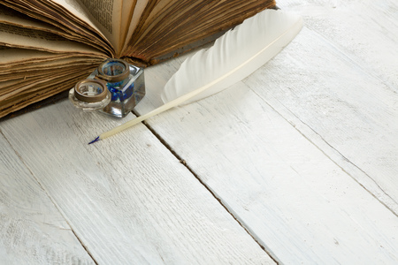 inkpot: Feather quill, blue ink pot and medieval book on a rustic white painted table Stock Photo