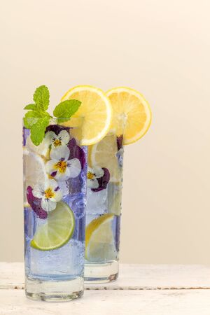edible: Cocktail drinks decorated with lemon and edible violet flowers