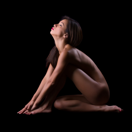 nudity: Implied nudity fine art image of a woman isolated on black