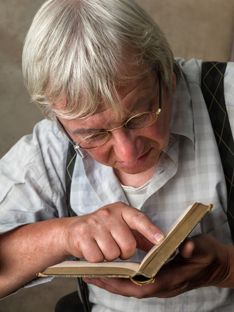 shortsighted: Elderly man with glasses reading a book