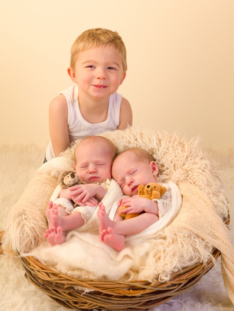 identical: Toddler boy posing with his newborn identical twin sisters Stock Photo