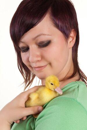 Happy teenager holder her yellow easter duckling in her hands photo