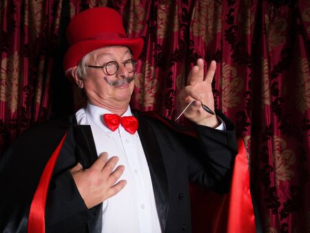 stage actors: Senior illusionist on stage bending a spoon Stock Photo