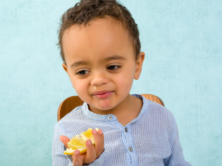 mixed race baby: Funny toddler with a snotty nose trying to eat a lemon