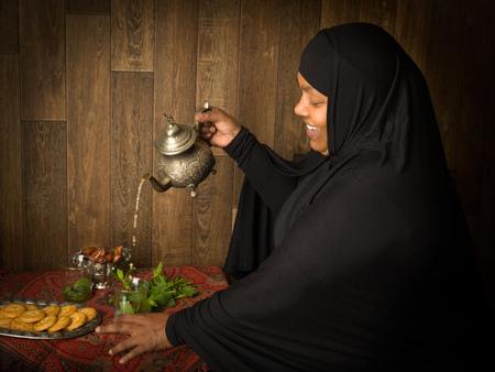 伝統: ミントお茶を注いだイスラム教徒の女性の伝統的な方法を笑顔 写真素材