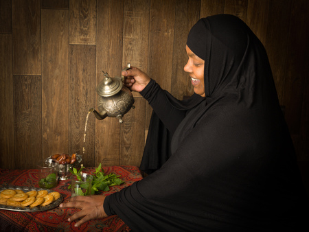 veiled: Smiling muslim woman pouring mint tea the traditional way