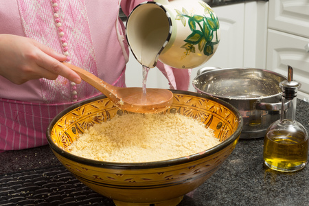 preparation: Couscous being prepared by a Moroccan immigrant woman in her modern European kitchen