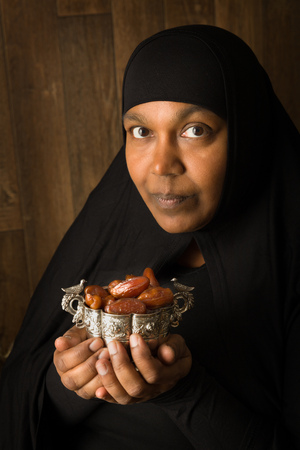 burqa: African muslim woman in black veil presenting traditional sweet dates
