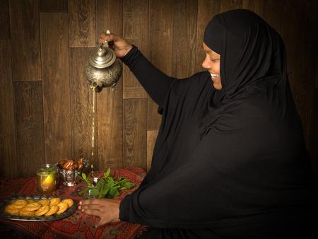 menta: Sonriendo musulmanes té de menta mujer vertiendo la manera tradicional