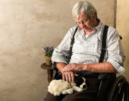 Old pensionné en maison de soins infirmiers à coucher avec son chien sur ses genoux Banque d'images