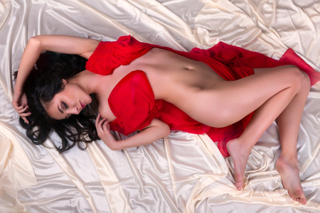 Relaxed woman lying naked on white and red satin