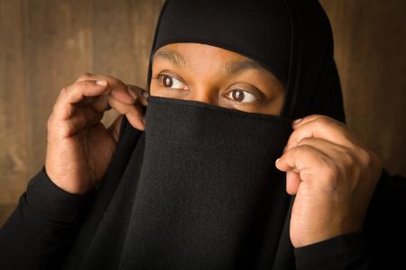 cultural clothing: African islam woman hiding behind a black veil