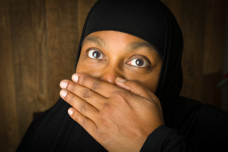 censorship: Muslim woman of African descent holding her hand in front of her mouth