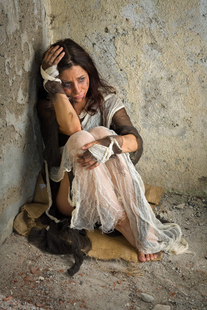 derelict: Abused and frightened woman sitting in the corner of a derelict building
