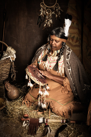 squaw: Weathered mature tribal female storyteller talking about heroic times