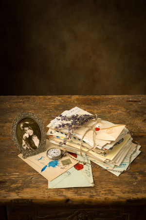 Antique portrait of a woman and a bundle of old letters on a wooden table photo