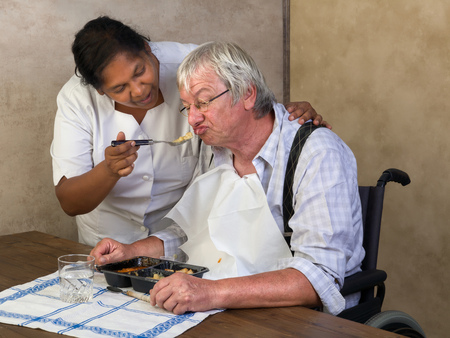 grumpy old man: Nurse in old peoples home trying to make a patient eat his dinner