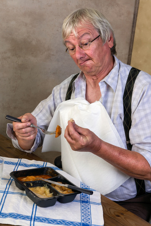funny elderly: Funny elderly man breaking a tooth while eathing his tv dinner