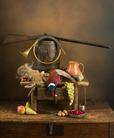 Autumn still life with hunting rifle, pheasant and hare Foto de archivo